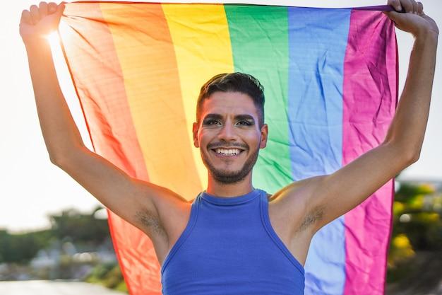 Трансгендерный мужчина с макияжем держит радужный флаг лгбт на закате - концепция лгбт