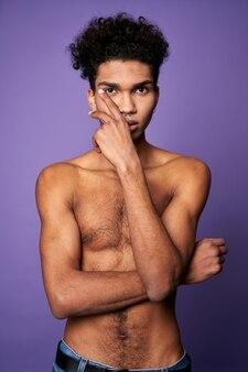 Трансгендерная модель позирует портрет молодого человека без футболки, изолированные на фиолетовом фоне