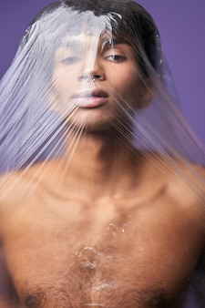 Transgender model with plastic bag on head portrait scared young man with claustrophobia problem