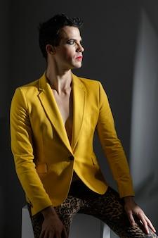 黄色のジャケットを着て目をそらしているトランスジェンダーの人