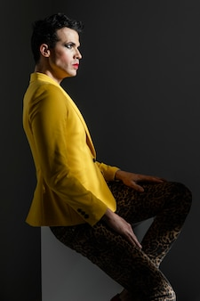 Transgender person wearing yellow jacket standing side view
