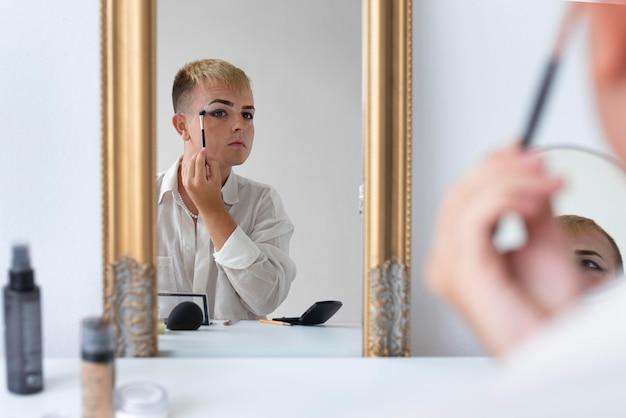 Transgender putting on makeup close up