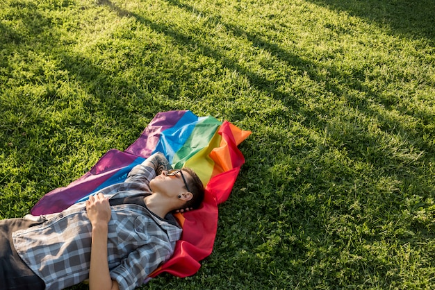 Transgender resting on green meadow