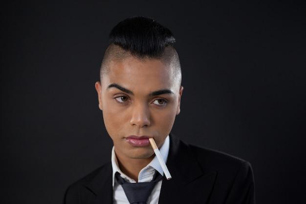 Трансгендер с сигаретой во рту над черной стеной