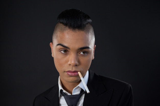 Transgender with cigarette in mouth over black wall