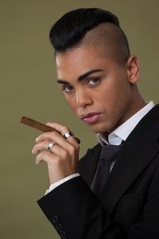 Transgender woman holding cigarette on green wall