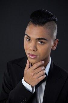 Трансгендерная женщина в полном люксе у черной стены