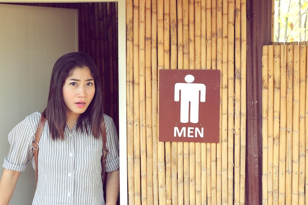 Transgender woman leave from the men's toilet looking straight and upset