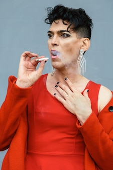 Transgender woman in red clothing, posing and smoking, with an wall of the street background. lgtb and fashion concept.