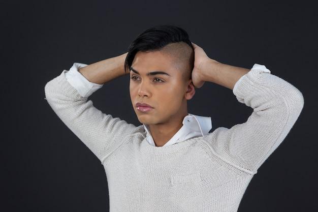 Трансгендерная женщина с поднятыми руками над черной стеной