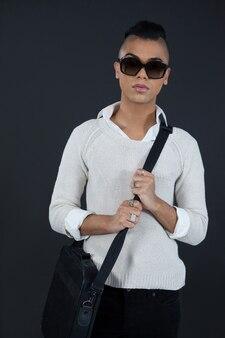 Трансгендерная женщина с сумкой у черной стены