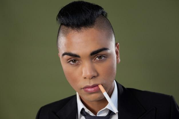 Трансгендерная женщина с сигаретой во рту над зеленой стеной