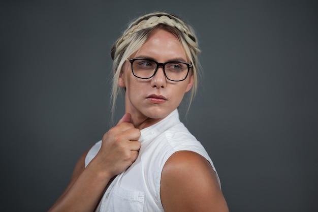 Трансгендерная женщина с прической смотрит в сторону