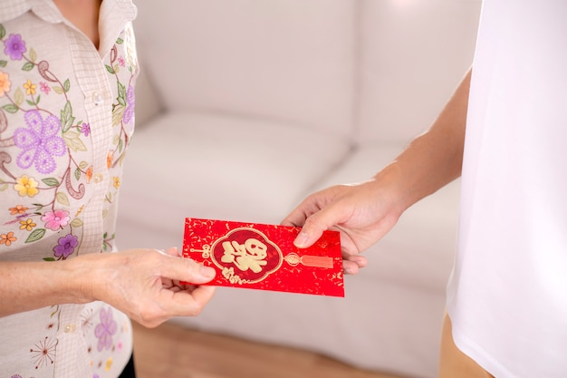 Translation text on red envelope in image: prosperity and spring.people parent giving red envelope for chinese new year