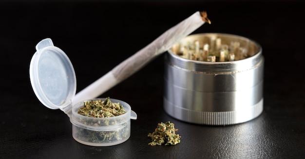 Transparent airtight dispenser with marijuana cigar and metal grinder on black background