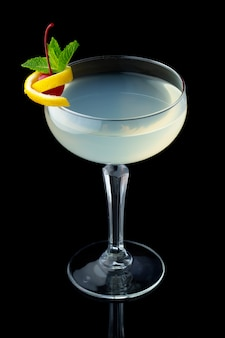 Transparent alcohol cocktail with mint and cherry isolated on black background