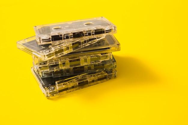 노란색 배경에 투명 오디오 카세트 테이프 스택