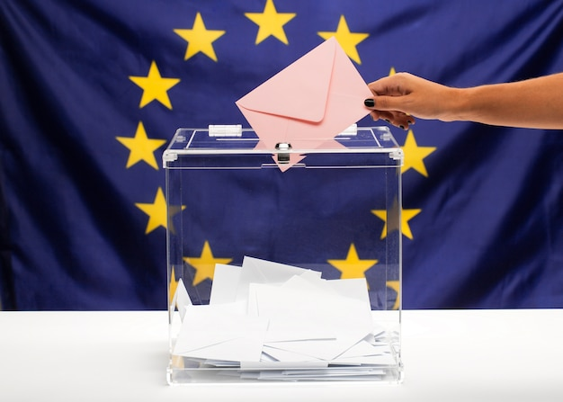 Transparent ballot box filled with pink envelope and european union flag