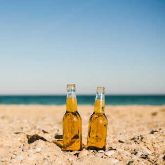 Transparent beer bottles in the sand at beach against clear sky