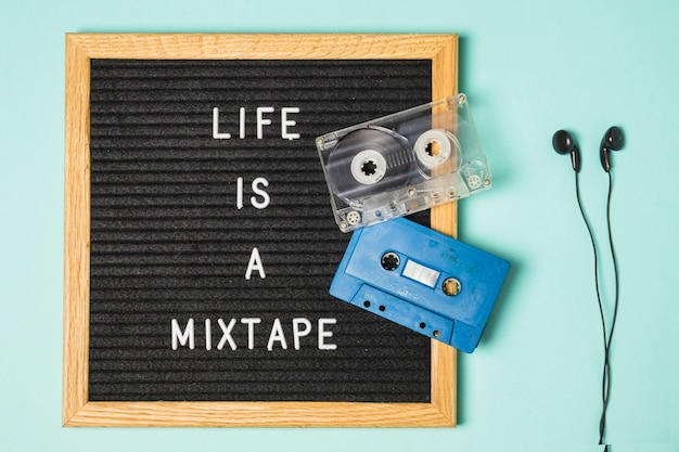 Transparent and blue cassette tape on message board with earphone on turquoise backdrop