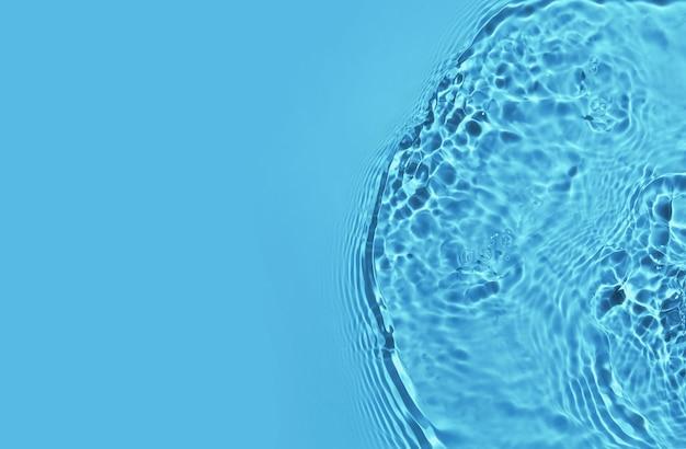 Прозрачная голубая водная поверхность с рябью, волнами и брызгами фона с копией пространства