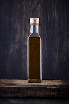 Transparent bottle filled with olive oil on dark backgrou