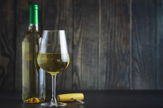 テーブルの上の白いドライワインの透明なボトル。木製の壁の背景に白ワイングラス。