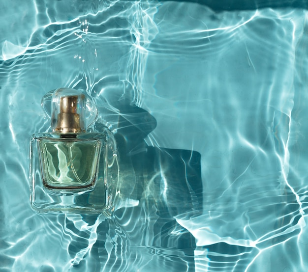 Transparent bottle perfume in blue water with shadows.