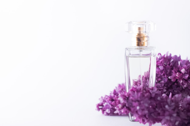 A transparent bottle of perfume in fresh spring violet lilac flowers