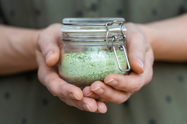 Ciotola trasparente di verdure essiccate verdi nelle mani di una persona
