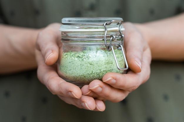 사람의 손에 녹색 말린 야채의 투명한 그릇