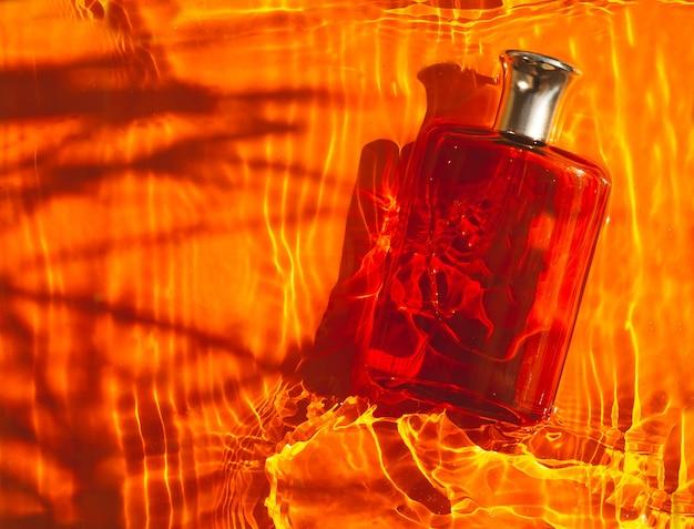 Прозрачный коричневый флакон духов в оранжевой воде с тенями. вид сверху