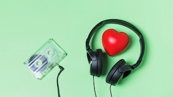 Transparent cassette tape connected with headphone around red heart