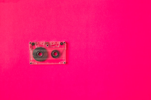 Transparent cassette tape on pink background