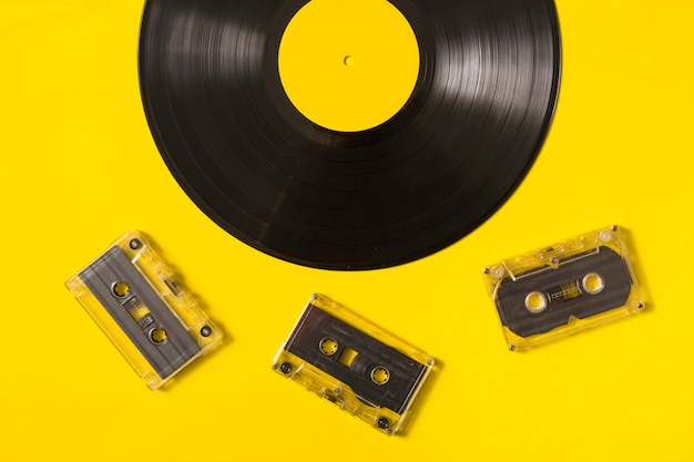 Transparent cassette taps and vinyl record on yellow background