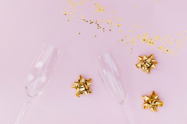 Transparent champagne glasses; golden bow and confetti on pink background