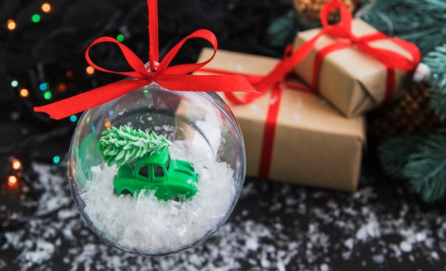 Transparent christmas ball inside with a toy car christmas tree on the roof