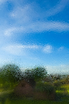 Transparent clean raindrops on the glass against the background of bright blue sky with clouds