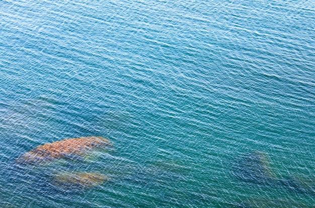 Прозрачная прибрежная лазурная водная гладь с камнями на дне