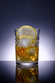 Transparent crystal glass with drink, slice of lemon and ice, advertising photography, selective focus