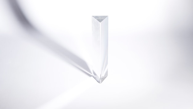 Transparent crystal prism in sunlight on white background