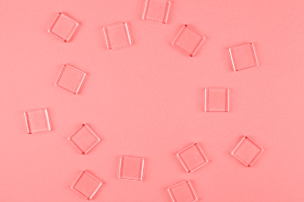 Transparent cubes arranged in circle shape against coral backdrop