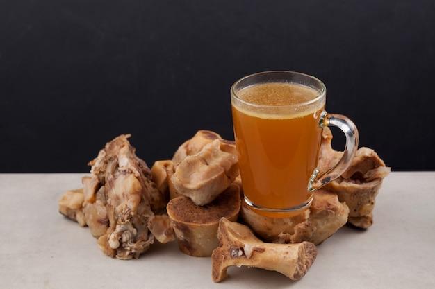 透明な骨スープのカップは、体に必要なアミノ酸を含むボイルドビーフの骨の上に置かれます。