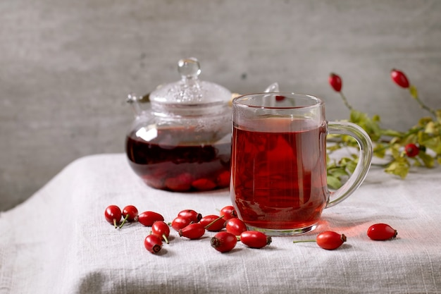 Transparent cup of rose hip berries herbal tea and glass teapot standing on white linen table cloth with wild autumn berries around. winter hot cozy beverage
