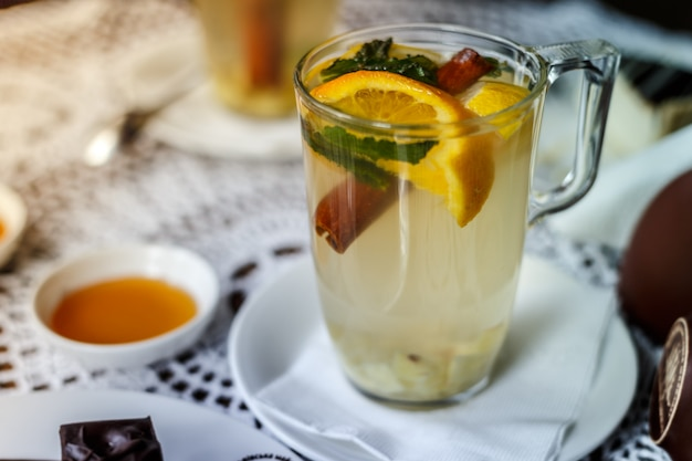 Transparent cup of tea with cinnamon, mint, orange on the table with a honey.