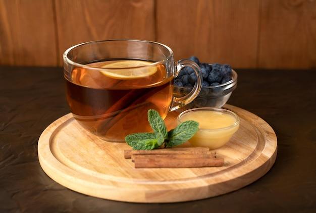 シナモンロールの近くの木製トレイに紅茶と透明カップ