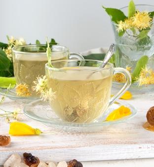 白い木製ボード上のリンデンからお茶と透明カップ