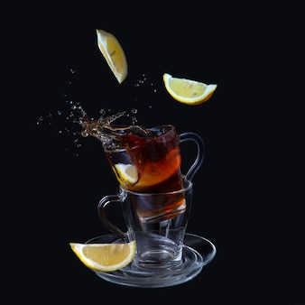 Transparent cups with tea. lemon slices fall into the cup. bursts, splashes.