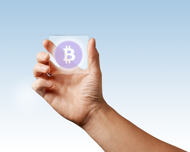 Transparent digital screen is held by a male hand with a bitcoin icon on a blue surface. business, technology and cryptocurrency concept