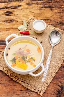 野菜のボウルに透明なアヒルのスープ。伝統的なブイヨン、健康的な食事。